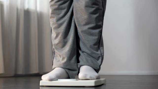 игривый пухлый самец, наступая на весы и поднимая ногу, хочет похудеть - вес стоковые видео и кадры b-roll