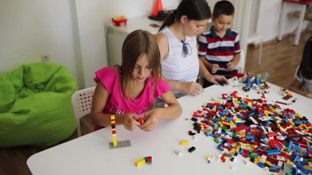 Playful preschoolers having fun with Lego Group of preschool kids are playing at a daycare center, having fun with colorful toy block playroom stock videos & royalty-free footage