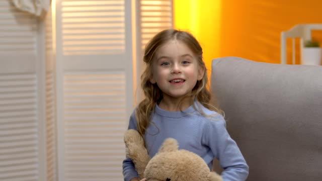 vídeos de stock e filmes b-roll de playful sweet little girl hiding behind plush toy, smiling to camera, happiness - teddy bear