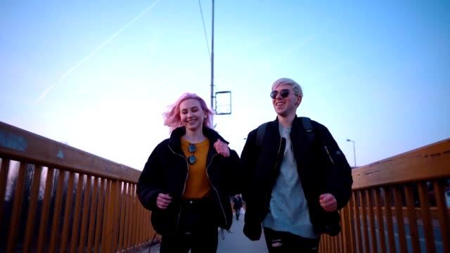 stockvideo's en b-roll-footage met speels tiener paar lopen - roze haar