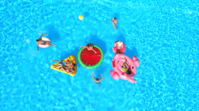 vídeos de stock e filmes b-roll de aerial: playful teenagers having fun on inflatable colorful floats in pool water - brinquedos na piscina
