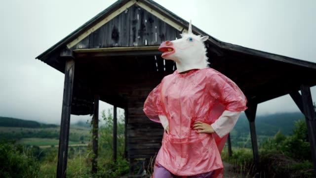 vídeos y material grabado en eventos de stock de unicornio juguetón en un impermeable - unicornio