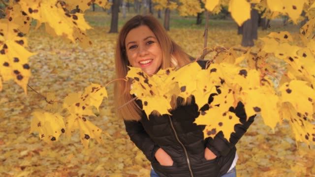 Playful Woman Hiding In Branches Tree With Yellow Autumn Foliage Gets Pleasure video
