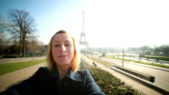 vídeos de stock, filmes e b-roll de alegre mulher tomando selfie na torre eiffel-sinal de paz - moda parisiense
