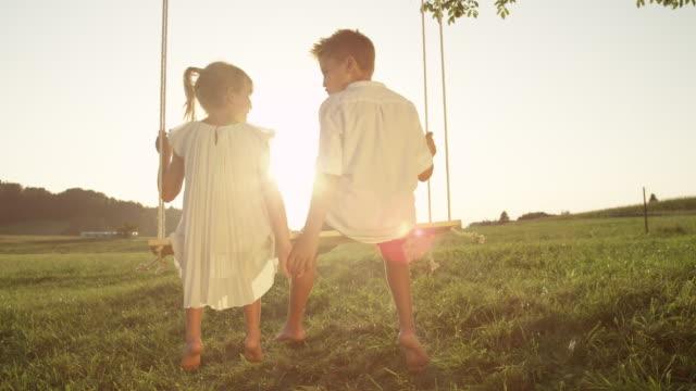 slow motion close up verspielten jungen und mädchen auf schaukel bei sonnenuntergang hand in hand - schaukel stock-videos und b-roll-filmmaterial