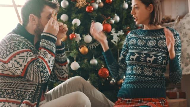 lekfull ungt par förbereder gåvor och dekorera julgran - pepparkaka bildbanksvideor och videomaterial från bakom kulisserna