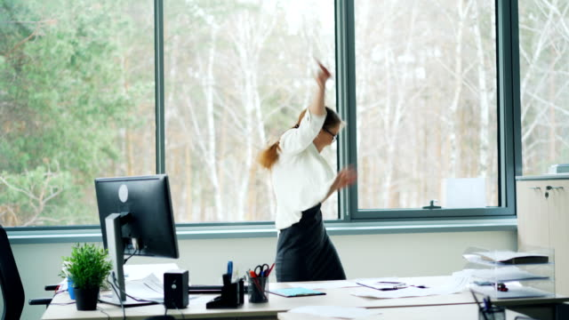 Playful young lady is dancing in office tossing her hair and taking off glasses having fun and laughing then walking away. Workplace, happy millennials and job concept.