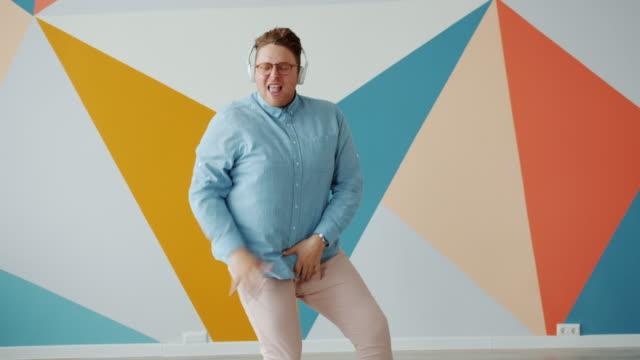 俏皮的年輕人跳舞在五顏六色的背景戴著耳機享受音樂 - 負面情緒 個影片檔及 b 捲影像