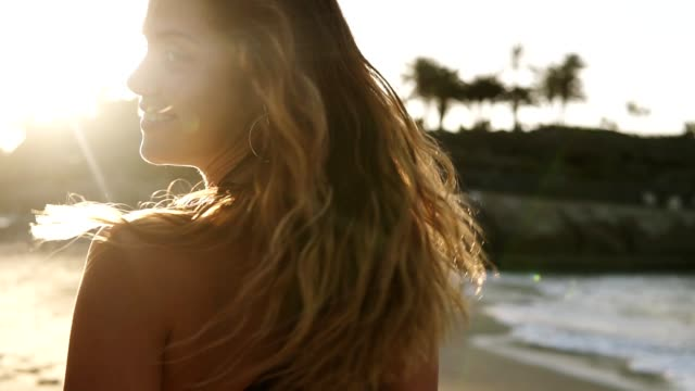 playful young woman enjoying summer vacation at summer beach. sensuous female with windswept hair is walking on beach at island wearing black bra by sea. looking back from a shoulder, turns around to smile. lens flares - spettinato video stock e b–roll