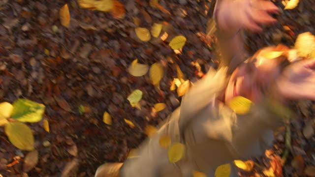 vídeos de stock, filmes e b-roll de jovem brincalhão jogando outono dourado deixa sobrecarga na floresta - setembro amarelo