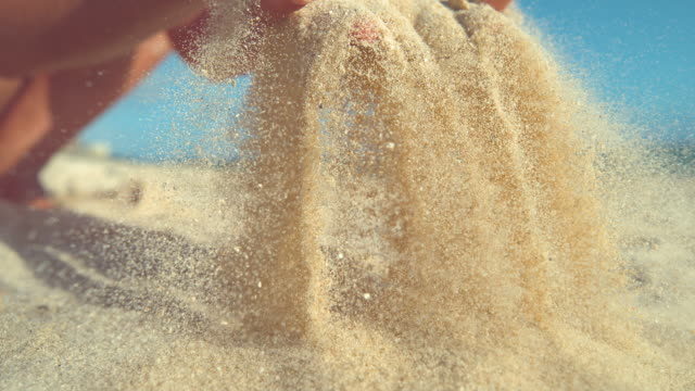 close up: playful young woman throws a handful of white sand over the camera. - piasek filmów i materiałów b-roll