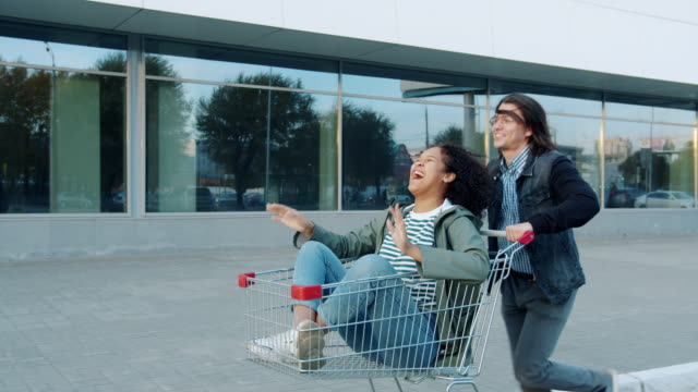Playful youth girl and guy having fun outdoors riding shopping cart laughing Playful youth girl and guy are having fun outdoors riding shopping cart laughing enjoying entertainment. Happiness, lifestyle and people concept. woman pushing cart stock videos & royalty-free footage