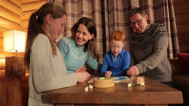 vídeos de stock, filmes e b-roll de jogar um jogo de tabuleiro com a família - game