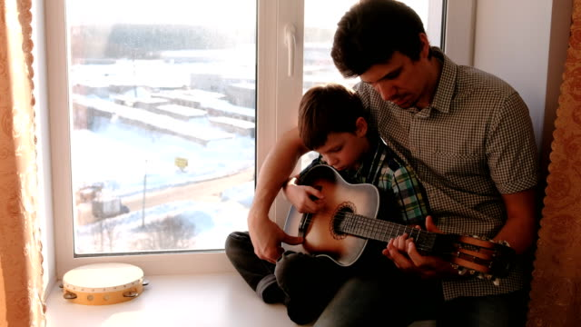 Playing a musical instrument. Dad teaches his son to play the guitar, sitting on the windowsill. video
