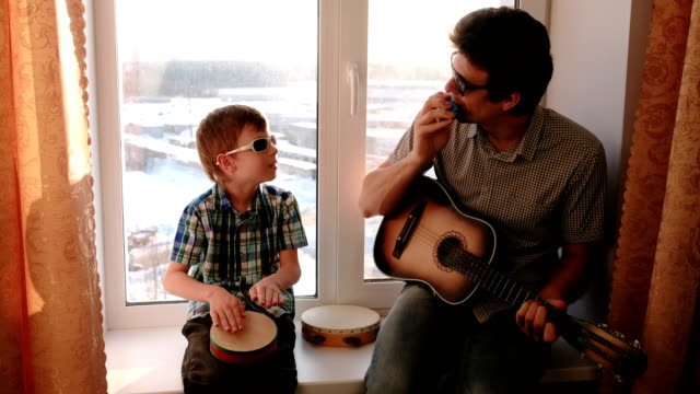 Playing a musical instrument in sunglasses. Dad is playing the guitar and son is playing drum sitting in windowsill video