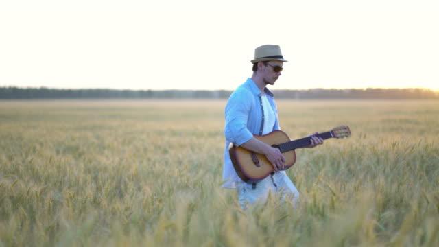 小麦畑で屋外でアコースティックギターを演奏。 ビデオ