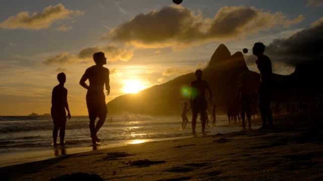 Playing beach football at sunset on Ipanema Beach, Brazil Group of people playing beach football at sunset on famous Ipanema Beach in Rio de Janeiro. Silhouettes with iconic mountains as background. Slow motion brazil stock videos & royalty-free footage