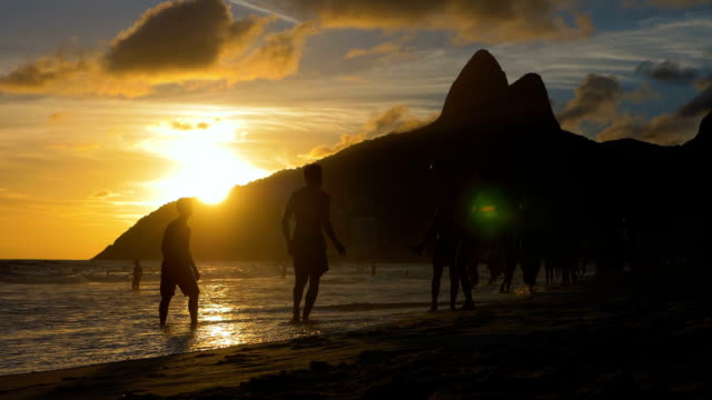 Jogando futebol de praia ao pôr do sol na praia de Ipanema, Brasil - vídeo