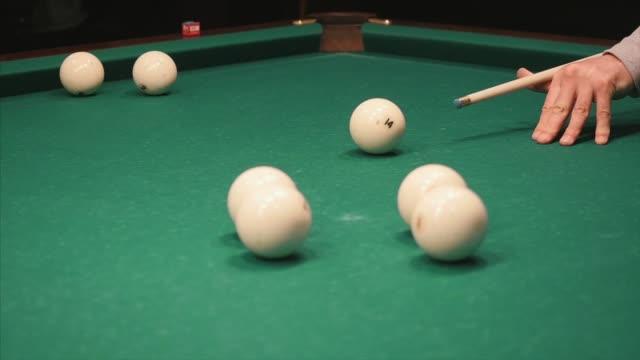 Playing billiards. Clip. Blowing a cue on the ball, the ball hit the pocket, the ball did not hit the pocket, billard, green table, breaking balls, muffled light, billiard club video