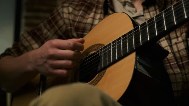 vídeos de stock, filmes e b-roll de jogando pela guitarra. jovem namorado. - música acústica