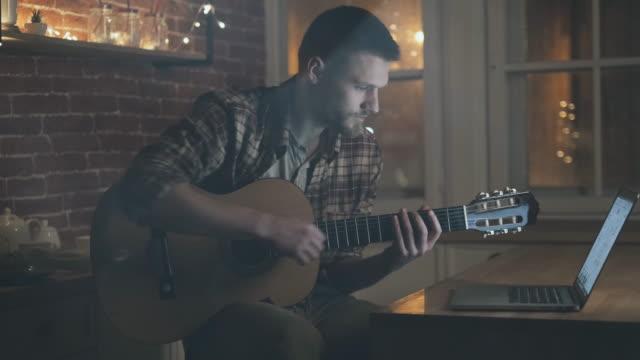 spela med gitarr. unga pojkvän. arbeta med laptop. - gitarr bildbanksvideor och videomaterial från bakom kulisserna