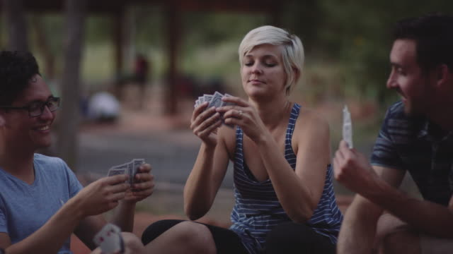 4K UHD: Playing Cards in the Campsite Two young couples sitting in their campsite and playing a card game playing card stock videos & royalty-free footage