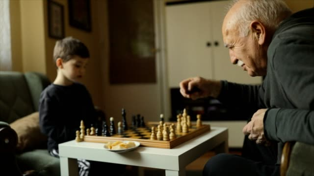 vídeos de stock e filmes b-roll de playing chess with grandfather - xadrez