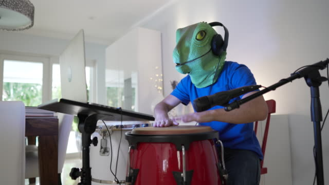 Playing congas and goofing around during a video call wearing a lizard mask
