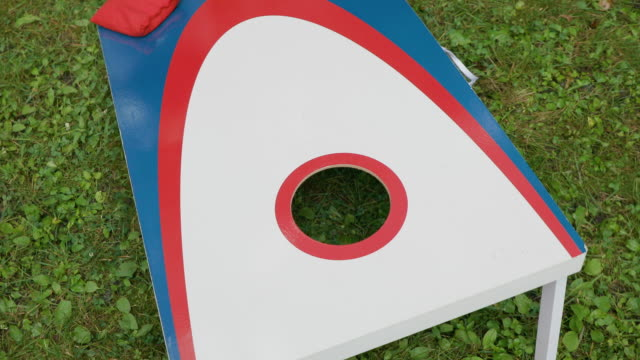 stockvideo's en b-roll-footage met spelen cornhole spel in de tuin met rode, witte en blauwe bord en tassen - vrijetijdsspel