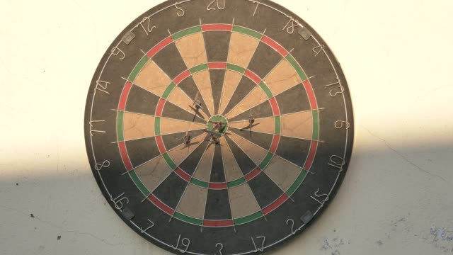 Playing dart in sunny day, and the last dart hits bulls eye in last shot, 4k footage, slow motion.