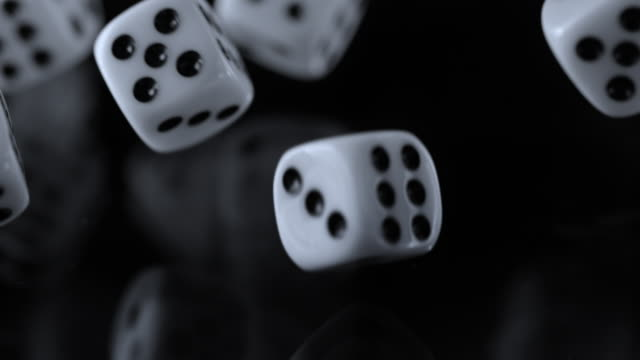 SLO MO LD Playing dice falling onto a black surface and rolling