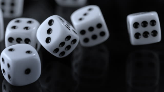 SLO MO Playing dice rolling around on a black surface