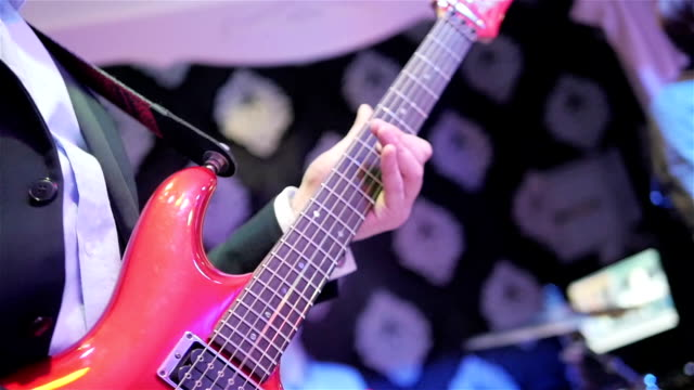 playing guitar close up slow motion. male hand fingers press chords holding notes on fretboard of new red shining electric guitar. guitarist performs live at concert club. rock star solo photo flashes - prom fashion stock videos and b-roll footage