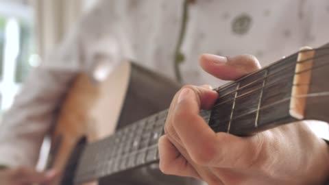 vidéos et rushes de jouer à la guitare fermer - doigt humain