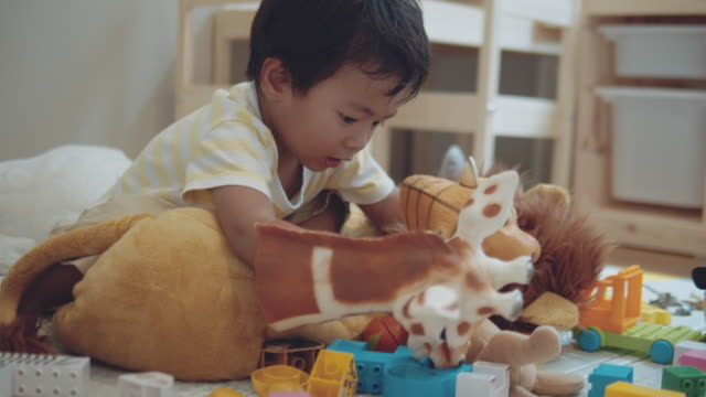 Playing Make Believe Children, people and education, Asian baby boy playing with animal doll on the floor in playroom at home. Bangkok, Thailand. playroom stock videos & royalty-free footage