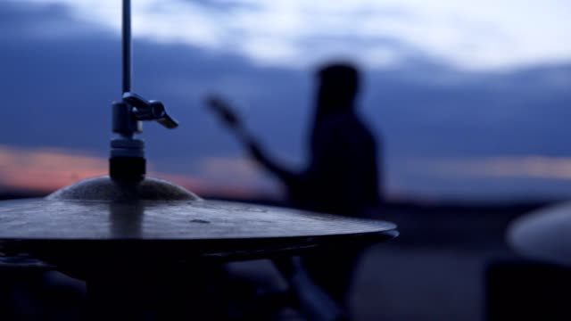 Playing on drums. Jam session after sunset