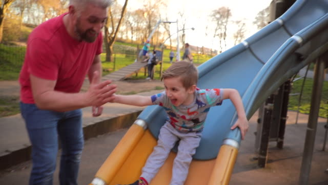 playing on the slide in the park - scivolo video stock e b–roll