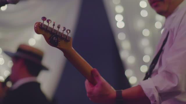 stockvideo's en b-roll-footage met het gitaarspelen, close up - oost aziatische cultuur