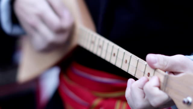 Playing the string balalaika Playing the string balalaika of a musician in national clothes russian culture stock videos & royalty-free footage