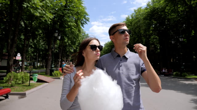Playing With Cotton Candy Man and woman in the park playing with cotton candy. Steadicam Shot. Summer sunny day. cotton candy stock videos & royalty-free footage
