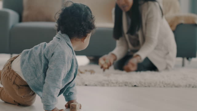 Playtime is a magical time 4k video footage of a woman playing with her baby at home crawling stock videos & royalty-free footage