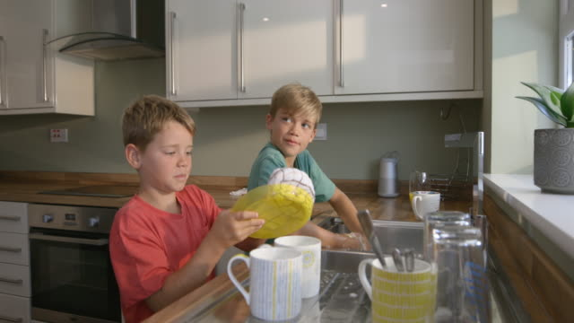 Playtime Washing Up A side-view shot of two young brothers washing the dishes together, they are splashing each other with bubbles. chores stock videos & royalty-free footage