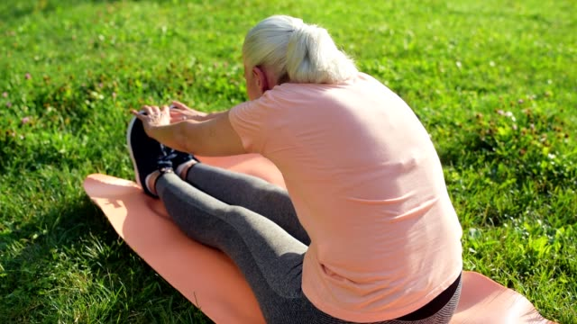 Pleasant aged woman doing stretching exercises in the park video