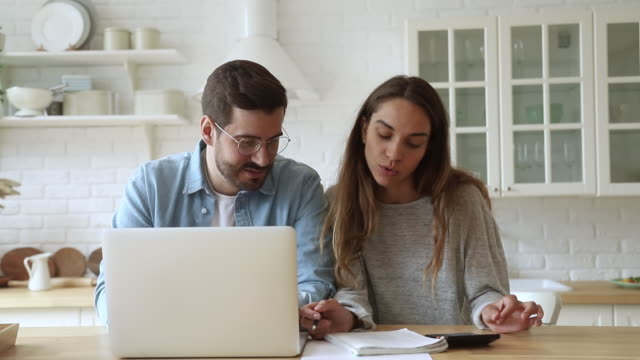 Pleasant focused young mixed race family spouses calculating payments.
