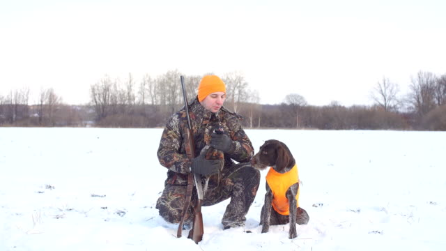 pleasant man is thanking his dog for help during hunting