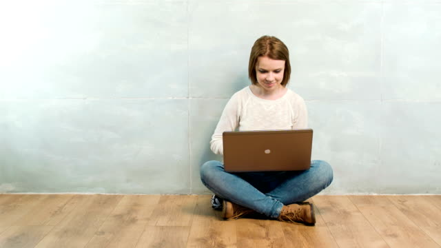 Pleasant woman sitting cross-legged with laptop Thinking about you. Pleasant smiling young lady sitting cross-legged with laptop on isolated background sideways glance stock videos & royalty-free footage