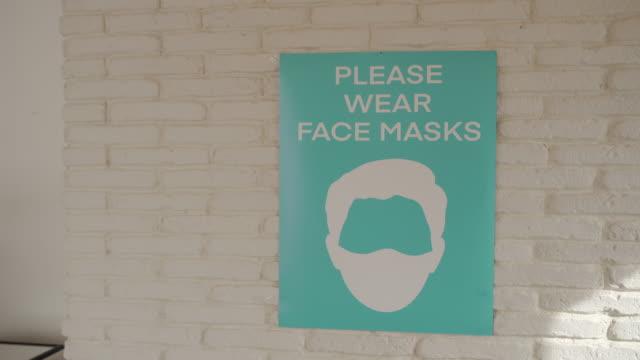 vídeos de stock, filmes e b-roll de por favor, use sinal de máscara facial na parede em um escritório moderno vazio - poster