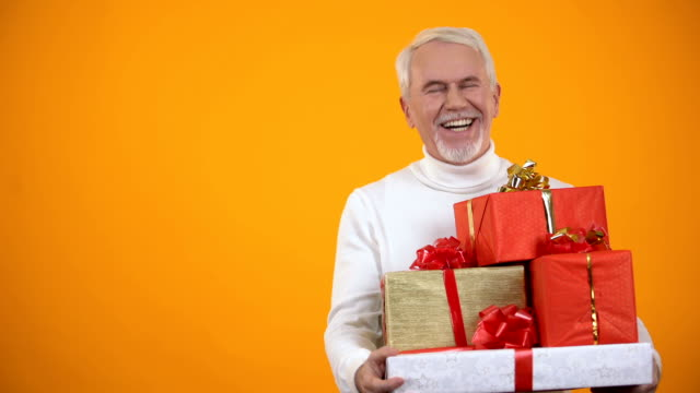Pleased elderly male holding giftboxes and smiling, big discounts on holidays Pleased elderly male holding giftboxes and smiling, big discounts on holidays birthday background stock videos & royalty-free footage
