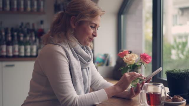 vídeos de stock e filmes b-roll de pleased senior woman holding a cup of tea while using laptop - senior business woman tablet