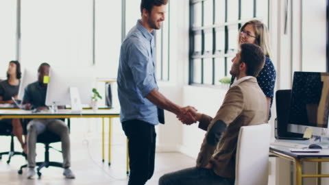 Pleased to have you part of the team 4K video footage of two coworkers shaking hands together in a modern office while a coworker looks on coworker stock videos & royalty-free footage